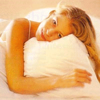 Woman sleeping with down filled pillow and quilt.